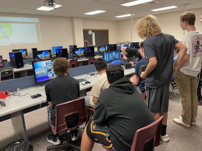 Gilbert High School esports members huddled around a computer, watching a match.