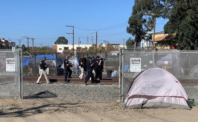 Salinas police comb through a homeless encampment near train tracks on Market and Main Street following the arrest of a wanted suspect.