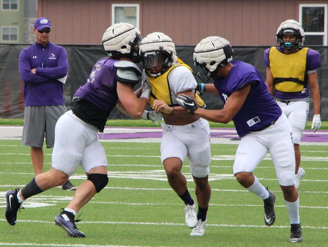 Coach Jon Anderson (left) looks on as his team runs through a special teams drill at USF practice on Wednesday at Bob Young Field.