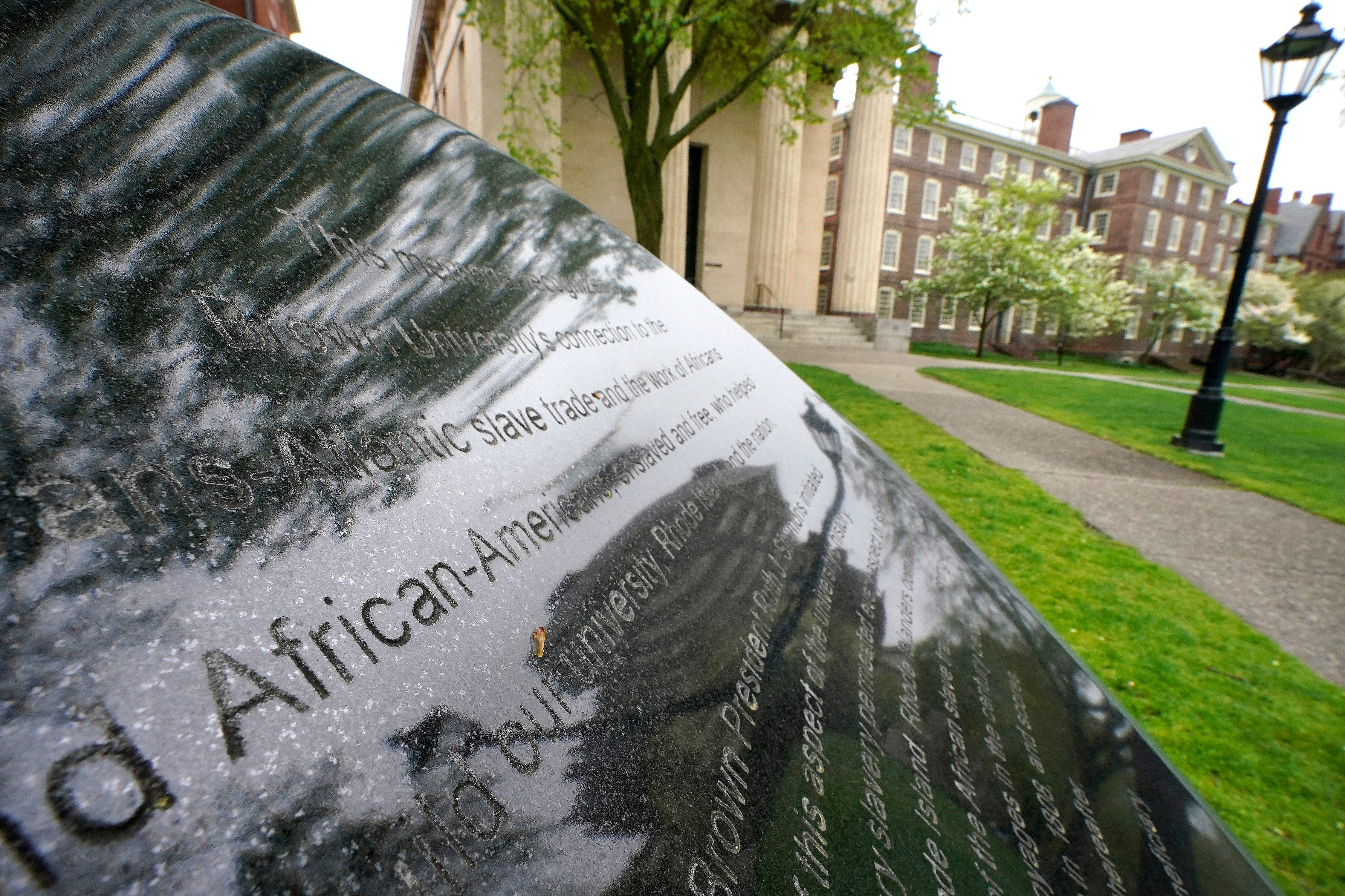 Words engraved on a stone plinth form a component of the Slavery Memorial by sculptor Martin Puryear, erected in 2014, on the Brown University campus in Providence, R.I., on Tuesday, May 4, 2021.