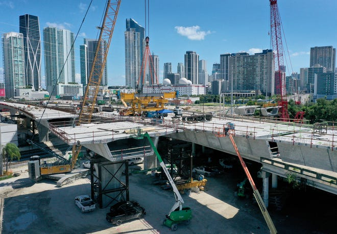 """MIAMI, FLORIDA - SEPTEMBER 27:  In an aerial view, construction workers build the """"Signature Bridge,"""" at I-95 and I-395 that replaces an older bridge on September 27, 2021 in Miami, Florida. The House of Representatives is expected to vote Thursday in Washington, DC on an infrastructure bill that includes $550 billion in new federal investment in America's infrastructure over five years. The bill designates $40 billion for bridge repair, replacement and rehabilitation.  (Photo by Joe Raedle/Getty Images) ORG XMIT: 775717289 ORIG FILE ID: 1343369484"""