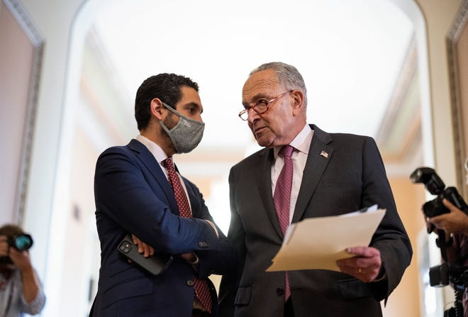 Senate Majority Leader Chuck Schumer, D.N.Y., speaks to an aide after the Democratic Policy Luncheon at the US Capitol in Washington, DC September 28, 2021