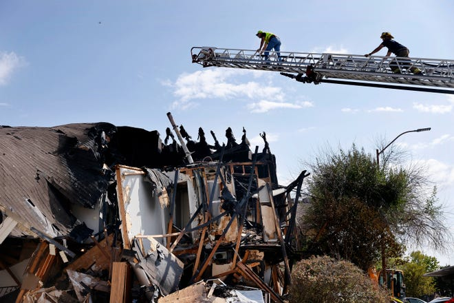 A Texas Railroad Commission official, left, is guided up an Dallas Fire and Rescue ladder truck by a firefighter to take scene photos following an apartment explosion on Highland Hills Drive in southeast Dallas, Wednesday, Sept. 29, 2021. A natural-gas explosion tore apart the building injuring people and firefighters who arrived on scene to investigate the smell of natural gas.