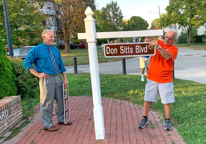 Don Sitts, CEO of Don Sitts Auto Sales Inc.,  puts up a sign that ceremoniously renames Broad Boulevard in his honor. Looking on is Cuyahoga Falls Mayor Don Walters.