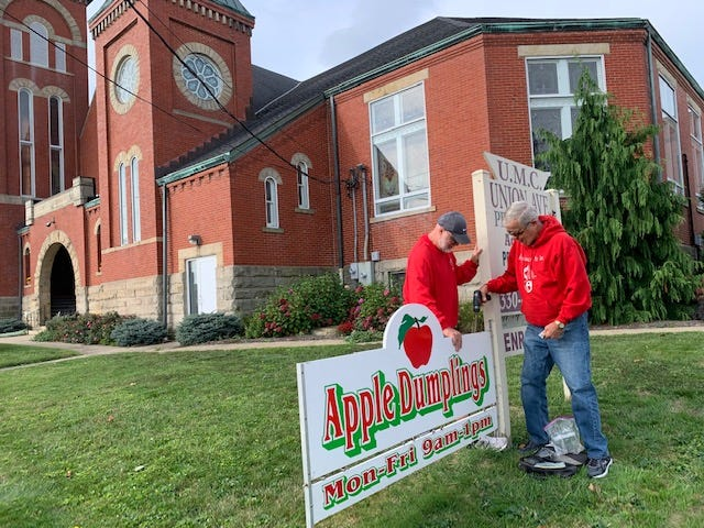 Jed Mewborn and Keith Brown install the sign announcing the start of apple dumpling sales in front of Union Avenue United Methodist Church.
