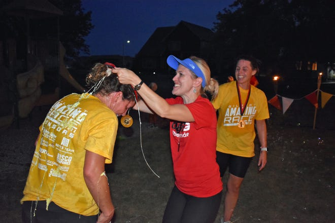 Covered with celebratory Silly String and water from local youngsters' squirt-guns, Gilbert Amazing Race winners Katie Hanson, left, and Amy Bell receive their medals from Ashley Brown. a member of the winning team from two years ago. The race was held Wednesday and ended at Banford Park in Gilbert.
