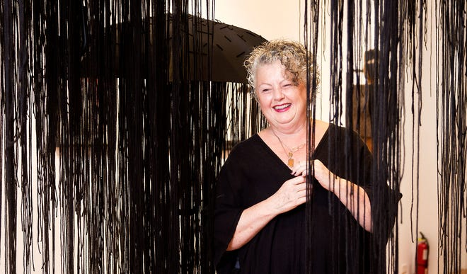Caren Petersen at her Short North art space, Not Sheep Gallery, on Tuesday, Sept. 28, with work by Izumi Yokoyama. The gallery will close at the end of October.