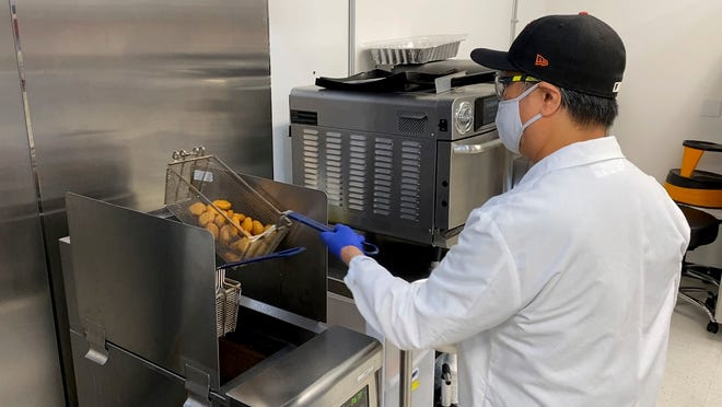 Nathan Foot, R&D chef at Impossible Foods, takes its new meatless nuggets out of a deep fryer in the company's test kitchen on Sept. 21, 2021 in Redwood City, Calif. The plant-based nuggets taste are designed to taste like chicken.
