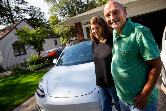 Jeff and Jill Raywood pose with their Tesla Model 3 on Thursday, Sept. 30, in their driveway in Holland.