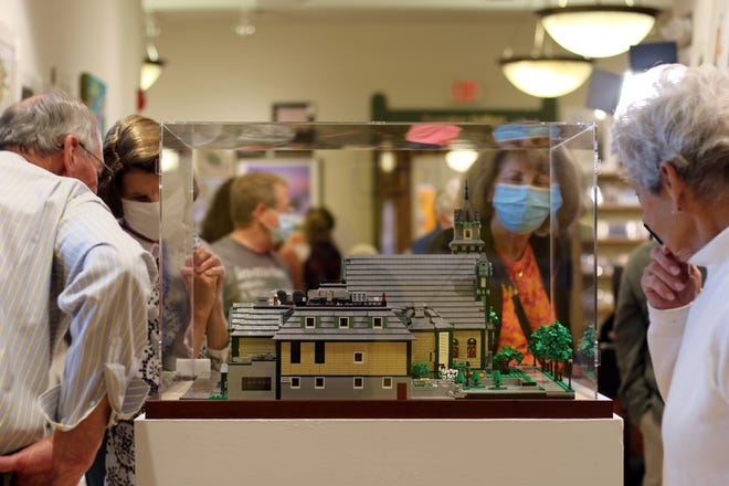 Guests of the Crooked Tree Arts Center in Petoskey look at the newly unveiled Lego model of the building on Wednesday, Sept. 29. The model was designed and built by local teen Roldan Grace.