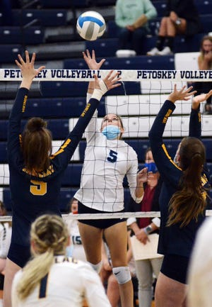 Petoskey's Raija Gross sends a tip shot over a pair of Cadillac blockers during Wednesday's Big North match in the Petoskey High School gym.