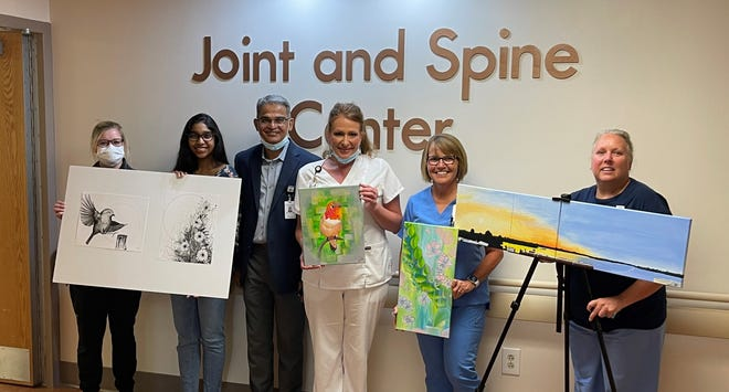 From left to right, Jessica Marston, RN, Artist Anika Kalluri, Dr. Prakasam Kalluri, Tracy Carrasquillo, RN, Barbara Stone, LPN, and Wendy Williams, NP pose for a photo in the Joint and Spine Center at  John Randolph Medical Center. The art collection is by Anika Kalluri.