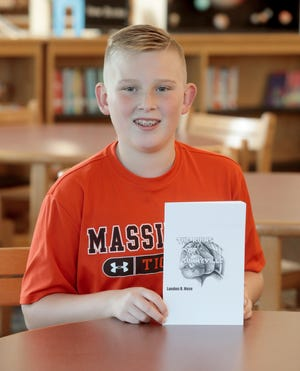 """Landon Hose, a sixth grader at Massillon Intermediate School, holds his first book, """"The Ruins of Sunnyville."""" The 11-year-old has sold more than 100 copies of his book on Amazon."""