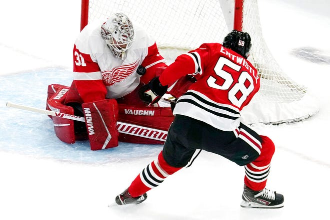 Detroit Red Wings goaltender Calvin Pickard, left, saves a shot by Chicago Blackhawks right wing MacKenzie Entwistle during the second period of an NHL preseason hockey game in Chicago, Wednesday, Sept. 29, 2021.