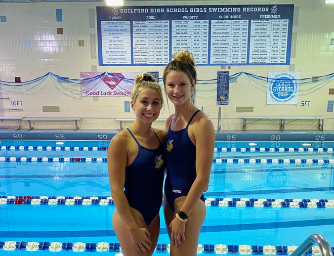 Ella Gasparini, left, and Mikayla Durkin, two Guilford swimmers who recently set pool or school records, stand next to the Guilford pool and in front of the record board on Wednesday, Sept. 29, 2021.