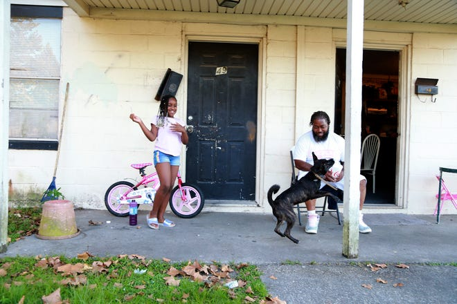 Nadawn Williams, 8, blows bubbles for Beast as her dad, Donald looks on outside the family's Clearview Homes apartment.