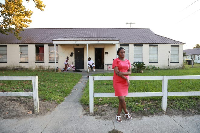 Natiema Challenger stands in front of her family's Clearview Homes apartment as her daughter Nadawn Williams, 8, and husband Donald play with their dog on the porch. On August 23 Clearview residents were given notice that they needed to vacate the properties by October 31.