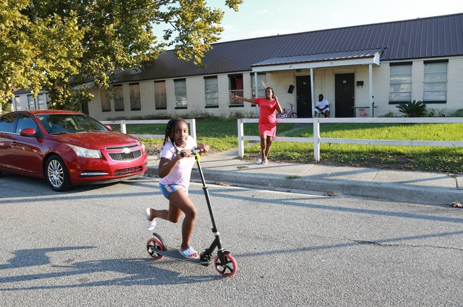 Nadawn Williams, 8, rides her scooter as her mom Natiema Challenger stands in front of the family's Clearview Homes apartment.