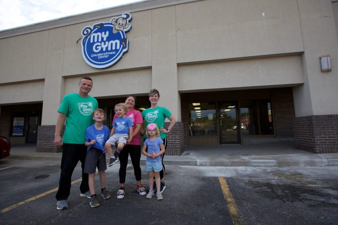 Troy Brown, left, and Cayla Brown, center, pose with their three children — Blake, 6, Dalton, 3, and Laurel, 4 — and My Gym trainer Kayla Schadegg outside the storefront, at 1921 S.W. Gage Blvd., that will soon be home to Topeka's first My Gym, a franchise dedicated to children's fitness.