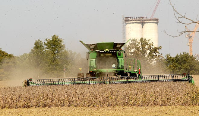 A combine stirs up a cloud of dust as a farm worker harvests cropland adjacent to State Road 60 West Wednesday afternoon.