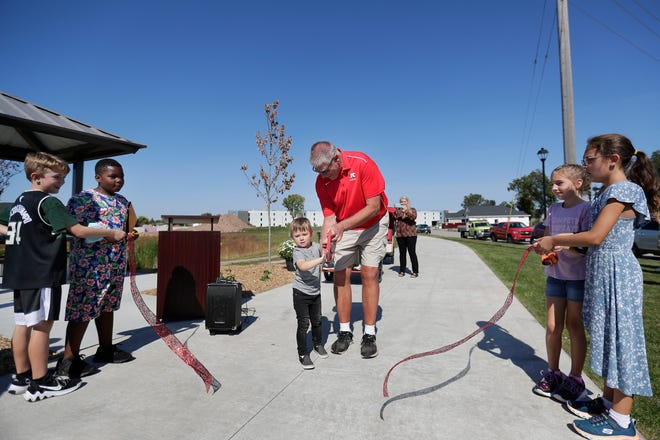 Retired village of Kimberly community enrichment director Al Schaefer, with help from his grandson Dax Geske and students from Westside Elementary School, cut the ribbon and officially open the Railroad Street Trail on Wednesday in Kimberly. The trail, part of the Loop the Locks trail system, connects the Kimberly riverfront to the CE Trail.
