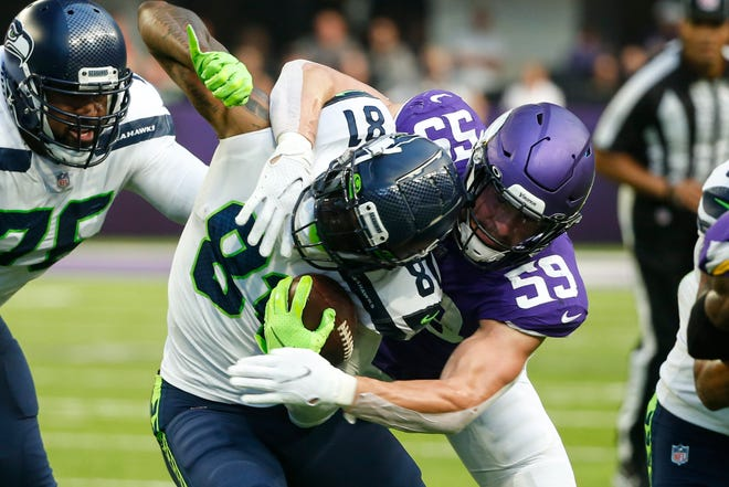 Minnesota Vikings outside linebacker Nick Vigil tackles Seattle tight end Gerald Everett in the first half of the Seahawks' loss in Minneapolis Sunday.