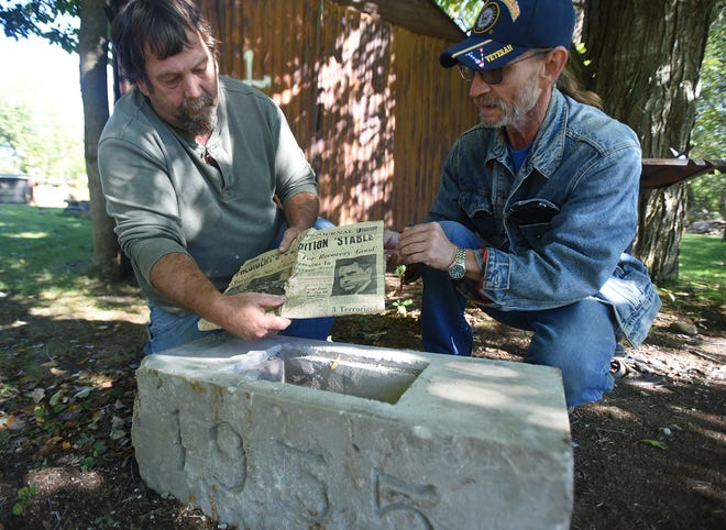 Rory Woodruff Sr. and Dan Bailey examine a Mansfield News Journal found inside a time capsule dated 1955.