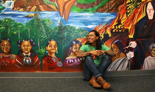 El artista local Sana Sana posa para un retrato frente a su mural en el Centro Multicultural en el campus de la Universidad de Nevada, Reno, el 30 de septiembre de 2021.