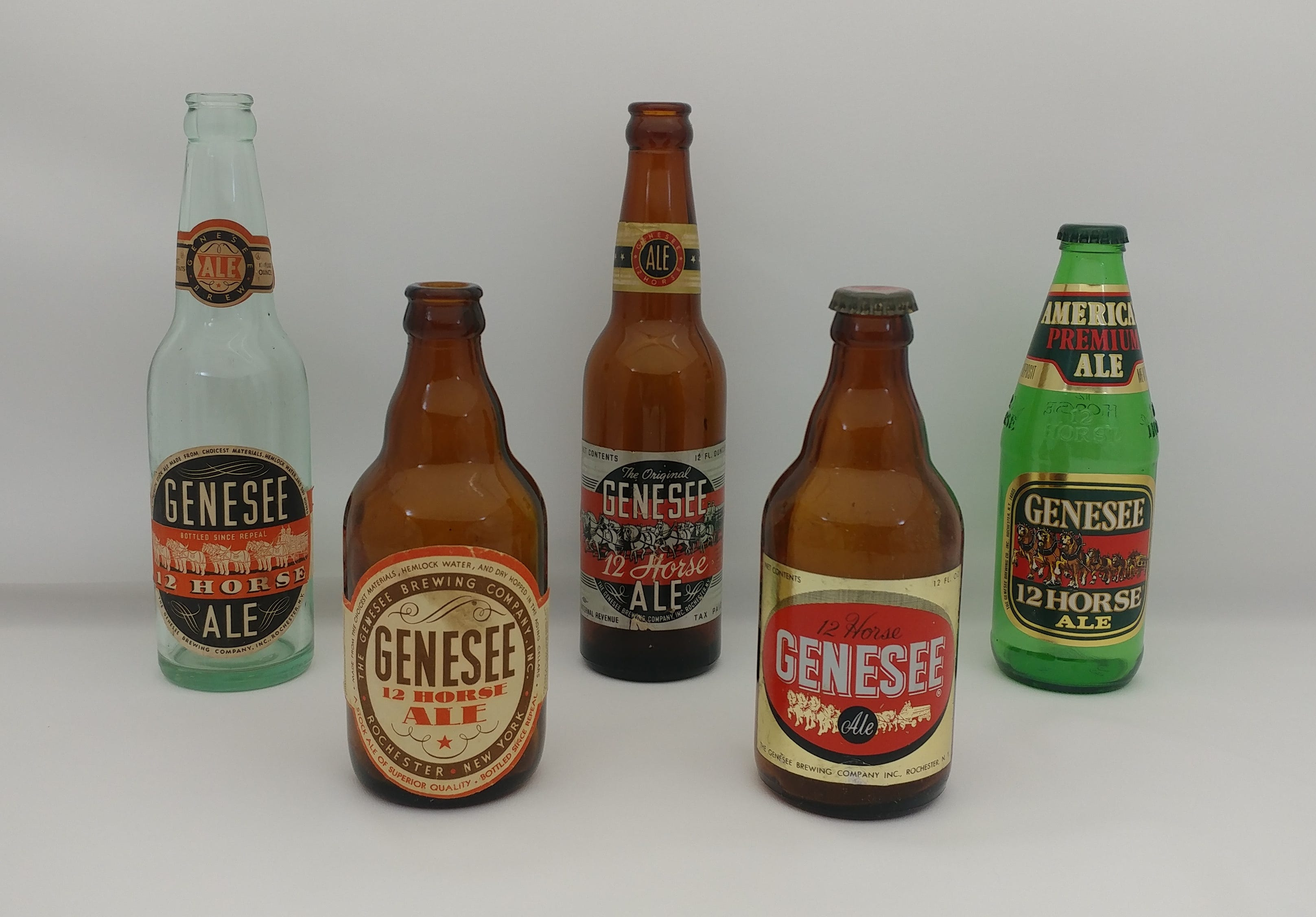 An assortment of Genesee 12 Horse Ale bottles through the years. From left to right: Clear bottle and middle left are between 1933 and 1936; Middle is from the 1940s; Middle right is mid to late 1950s; Right is from 1982.