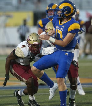 Angelo State University quarterback Hagen Garvin gets a pass off before getting hit by a Midwestern State player at LeGrand Stadium at 1st Community Credit Union Field on Saturday, Sept. 18, 2021.