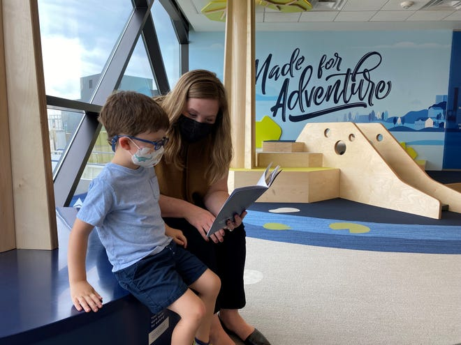Henry, 4, and mother Alaina Hardie check out the imagination and learning activity books at the new Adventure Play Space at the Sioux Falls Regional Airport on September 29, 2021.
