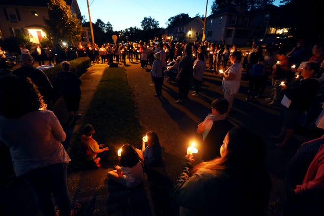 """Family and friends of Marcus Gaiters gathered at the corner of Myrtle and Lenox avenues Wednesday evening to pray for the 10-year-old. Gaiters has been battling COVID-19 for more than a month at Children's Hospital. """"Each face, each life, each candle held here tonight represents someone who cares deeply about this family"""" said Pastor Mark Ballmer told the crowd."""
