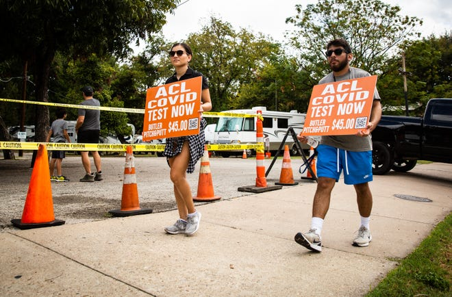 """Alexandra Villanueva, left, and Gilbert Reyes from RX Rapid Testing walk Friday down Barton Springs Road, outside the entrance to Austin City Limits Music Festival, advertising COVID-19 testing. A negative test or proof of vaccination is required for the festival this year. """"We've been out here since ten this morning and all day yesterday,"""" said Villanueva. """"There were twenty people in line when we opened this morning."""""""