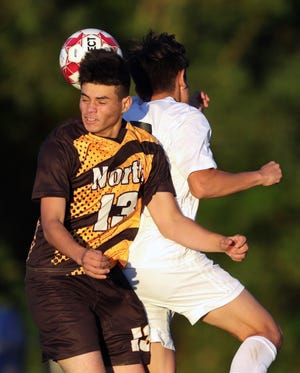 North's Alex Reyes heads the ball against a Painesville Harvey player during the second half of the Vikings' 2-1 loss on Thursday. [Jeff Lange/Beacon Journal]