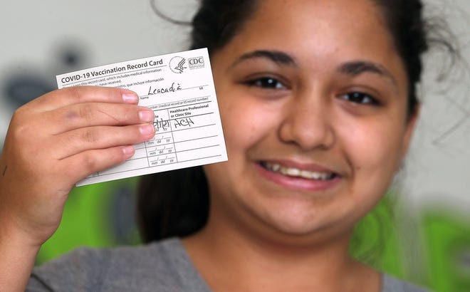 Leacadia Postlethwaite, 13, shows her COVID-19 vaccination card after getting her first dose Friday at Innes Community Learning Center in Akron.
