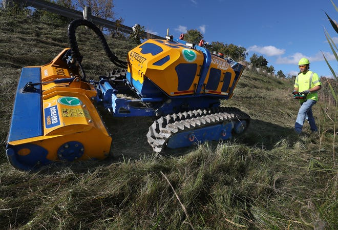 Cameron Brake, an ODOT worker, walks behind the Flailbot mower as it cuts grass on an embankment along I-480 eastbound in Twinsburg.
