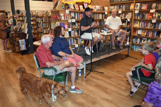 During a book relaunch at Dog-Eared Books in downtown Ames on Aug. 28, Lovie the golden retriever passes by the speakers, left to right, retired Iowa State head track coach and founder of Championship Productions Bill Bergan, sportswriter Brandon Hurley, NBA Coach Nick Nurse and co-CEO of Championship Productions Darryl Bennett.
