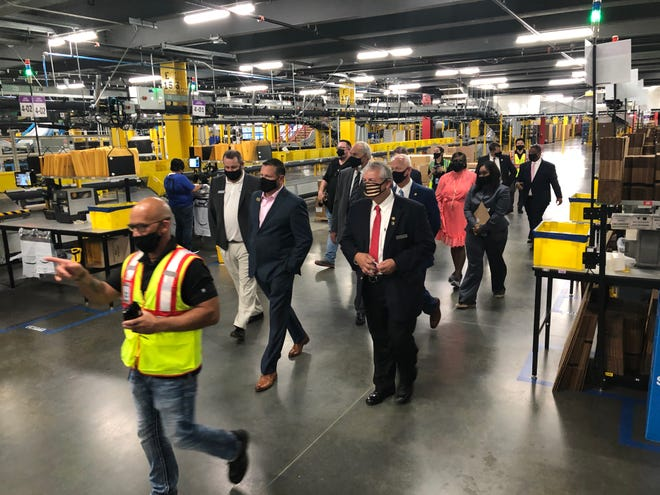 Amazon site manager Neil Gwynne (left) leads Columbia County officials through the 450,000-square-foot robotic fulfillment center that officially opened between Appling and Harlem on Friday.