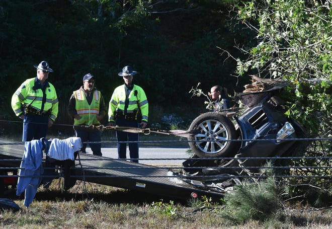 State Police look on as the rear end section of a Toyota sedan is pulled out from under a tree in the Route 6 median strip in Sandwich Friday morning at the scene of the fatal accident.