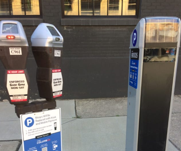 The city of Columbus has put signs on parking meters in East Franklinton, including this one in front of the Idea Foundry, 421 W. State St., warning motorists that the meters will soon be removed. Motorists will have to pay for parking using kiosks like the one that has been installed to the right, as well as through mobile payments.
