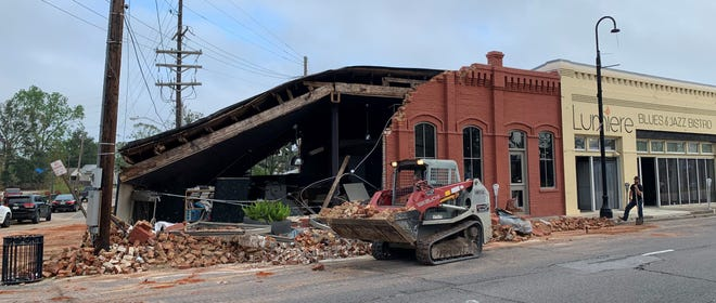 Workers clear debris Oct. 1 from a building on Main Street in downtown Houma wrecked by Hurricane Ida. The restaurant next door has reopened.