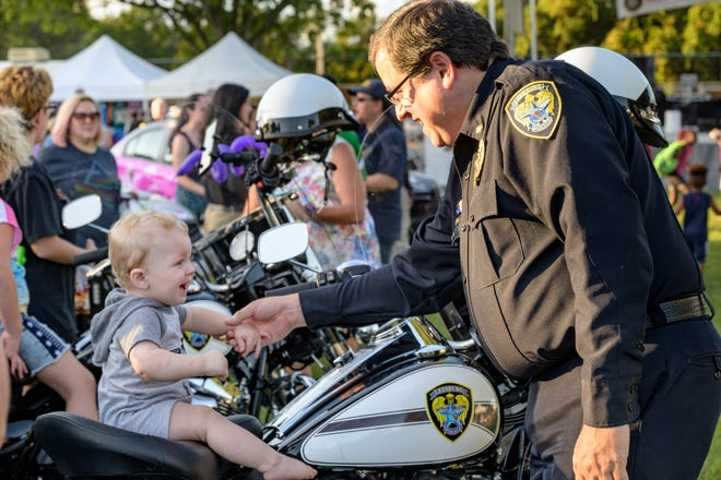 An officer helps a boy sit on a police motorcycle at the Leesburg Police National Night Out on in 2019.