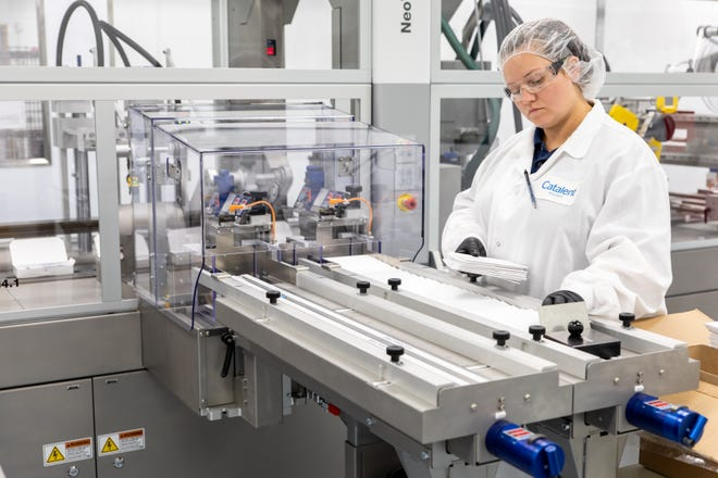 A Catalent employee working on a machine that packages final vials and syringes.