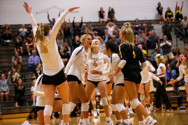 The Zeeland East volleyball team celebrate together after a comeback win against rival Zeeland West Thursday, Sept. 30, 2021, at Zeeland East High School.