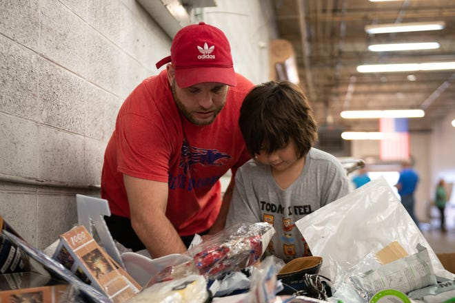 Father and son Vincent Gonzaga Sr. (left) and Jr., 7 (right), dig through a bin at Kairos Wholesale warehouse in Hutchinson.