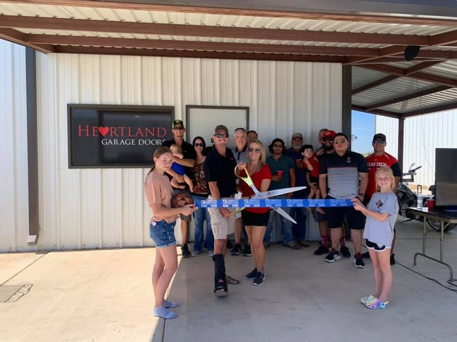 Heartland Garage Doors , 9120 FM 1585 Wolfforth. Holding scissors are owners Courtney and Amy Gage. Holding ribbon are the owners' children. Others pictured are vendors, staff, family and friends.