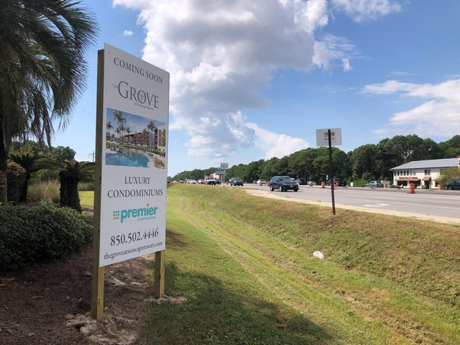 As traffic moves along U.S. Highway 98 in Miramar Beach on Friday, a sign announces a new condominium development, The Grove at Seascape Resort. Walton County officials last week heard from residents of Miramar Beach concerned about development-related pressures on the community.