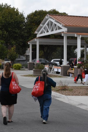 Participants carry their free tote bags to Legacy Square during Ladies Night Out