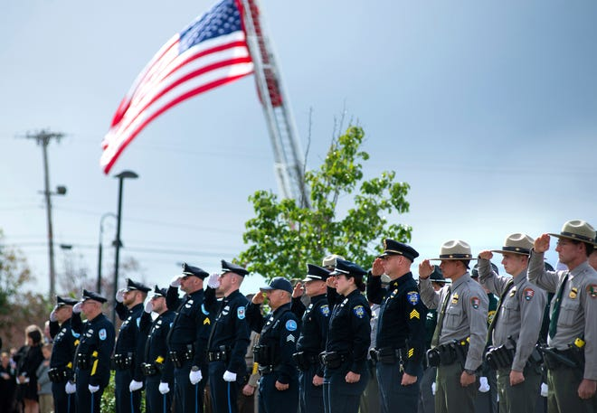 Law enforcement personnel salute in front of the Cross Insurance Center during a funeral service of Hancock County Sheriff's Deputy Luke Gross , Thursday, Sept. 30, 2021, in Bangor, Maine. Gross, 44, a veteran Hancock County sheriff's deputy, was struck and killed by a pickup truck while responding to a car crash in Trenton on Sept. 23.