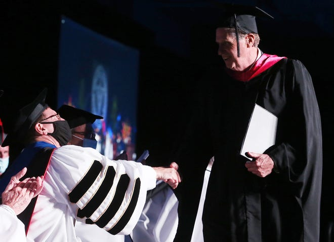 The Rev. Kenneth R. Sicard, 13th president of Providence College, is greeted by Gov. Dan McKee after the governor delivered a speech Friday at Sicard's inauguration.